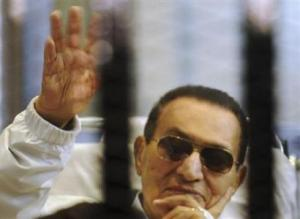 Former Egyptian President Mubarak waves inside a cage in a courtroom at the police academy in Cairo