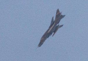 Jet belonging to the forces of Syrian President Bashar Al-Assad is seen in the sky during an air strike in the Hama countryside